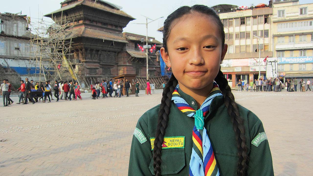 En ung, nepalesiska flicka, står scouting kostyp på sig