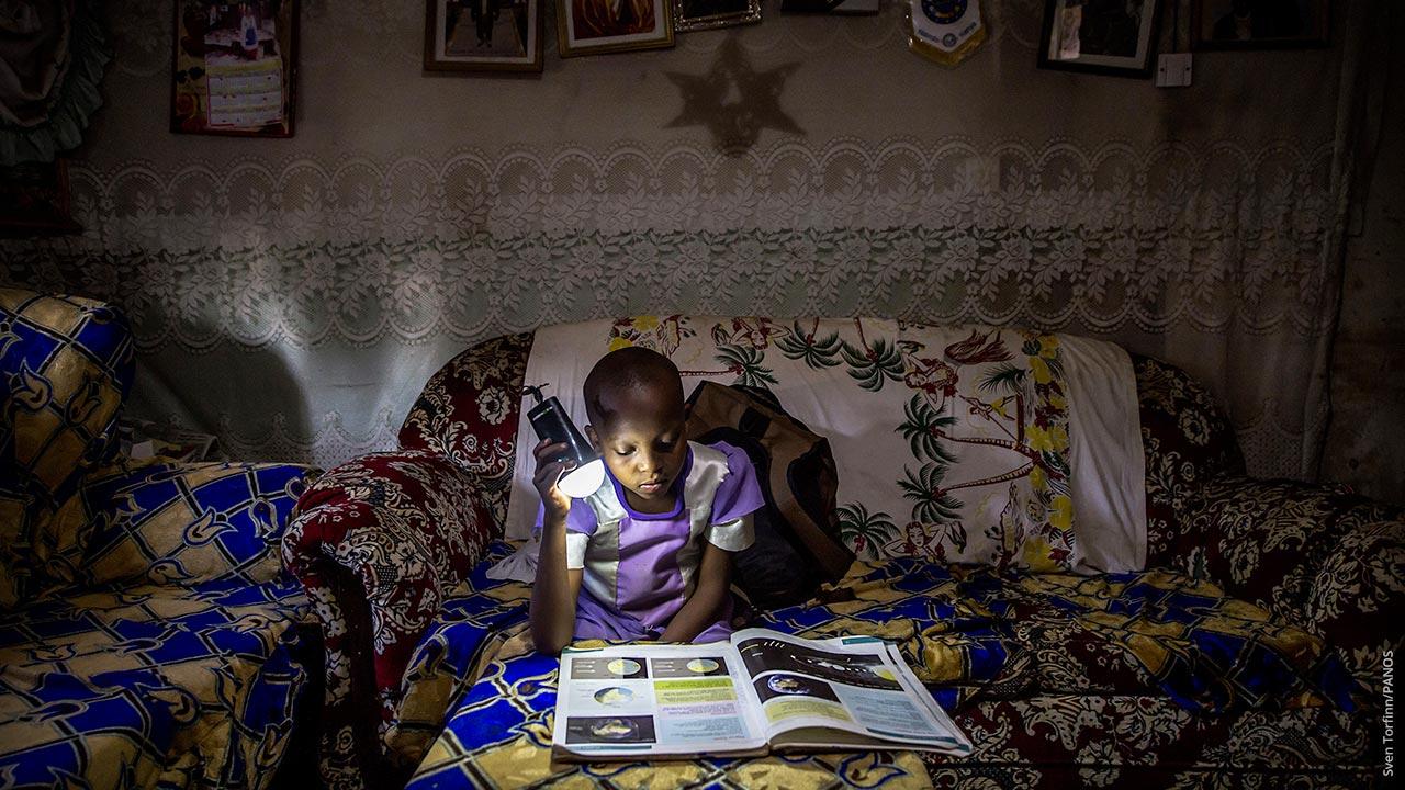 En tanzaniska flicka studerar en skolbok med lysande ficklampa