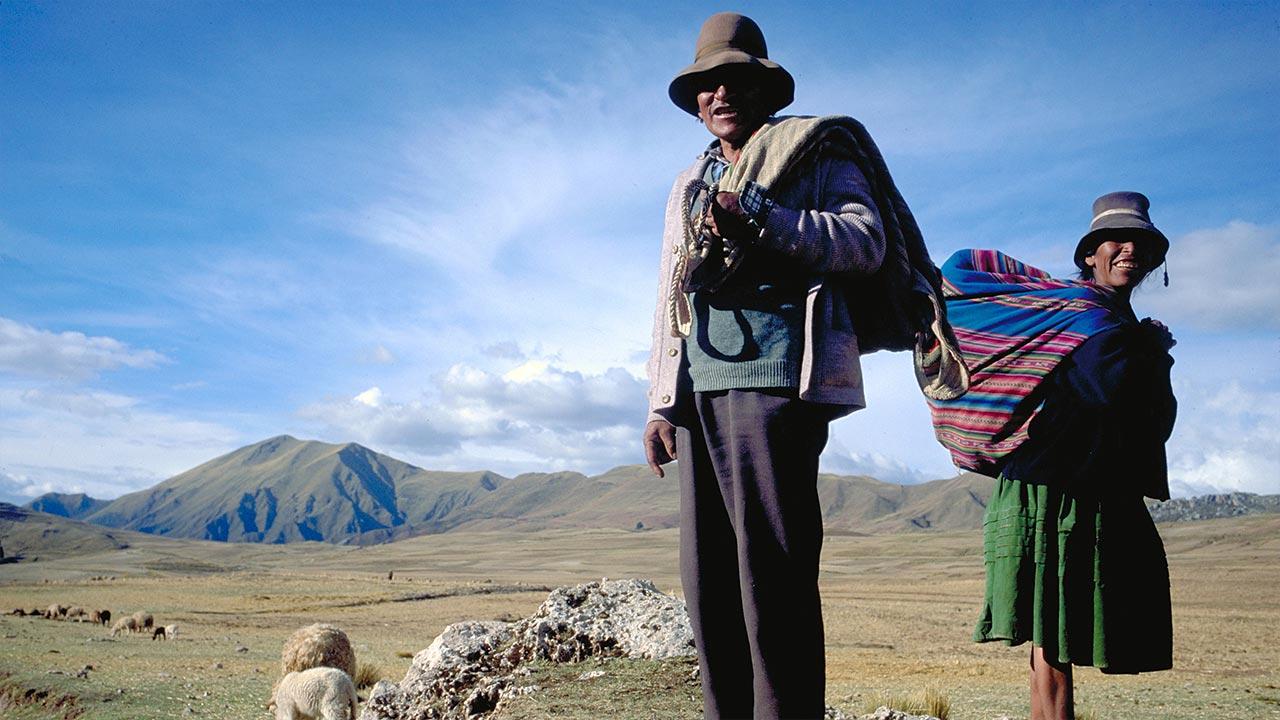 Ett par står på en kulle, får och berg i bakgrunden