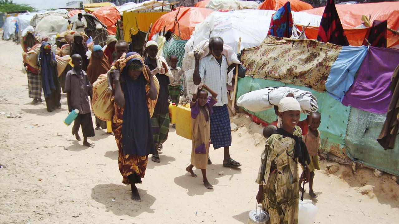 Olika ålders människor går med bagage på ryggen och i handen, i bakgrunden finns ett flyktingläger